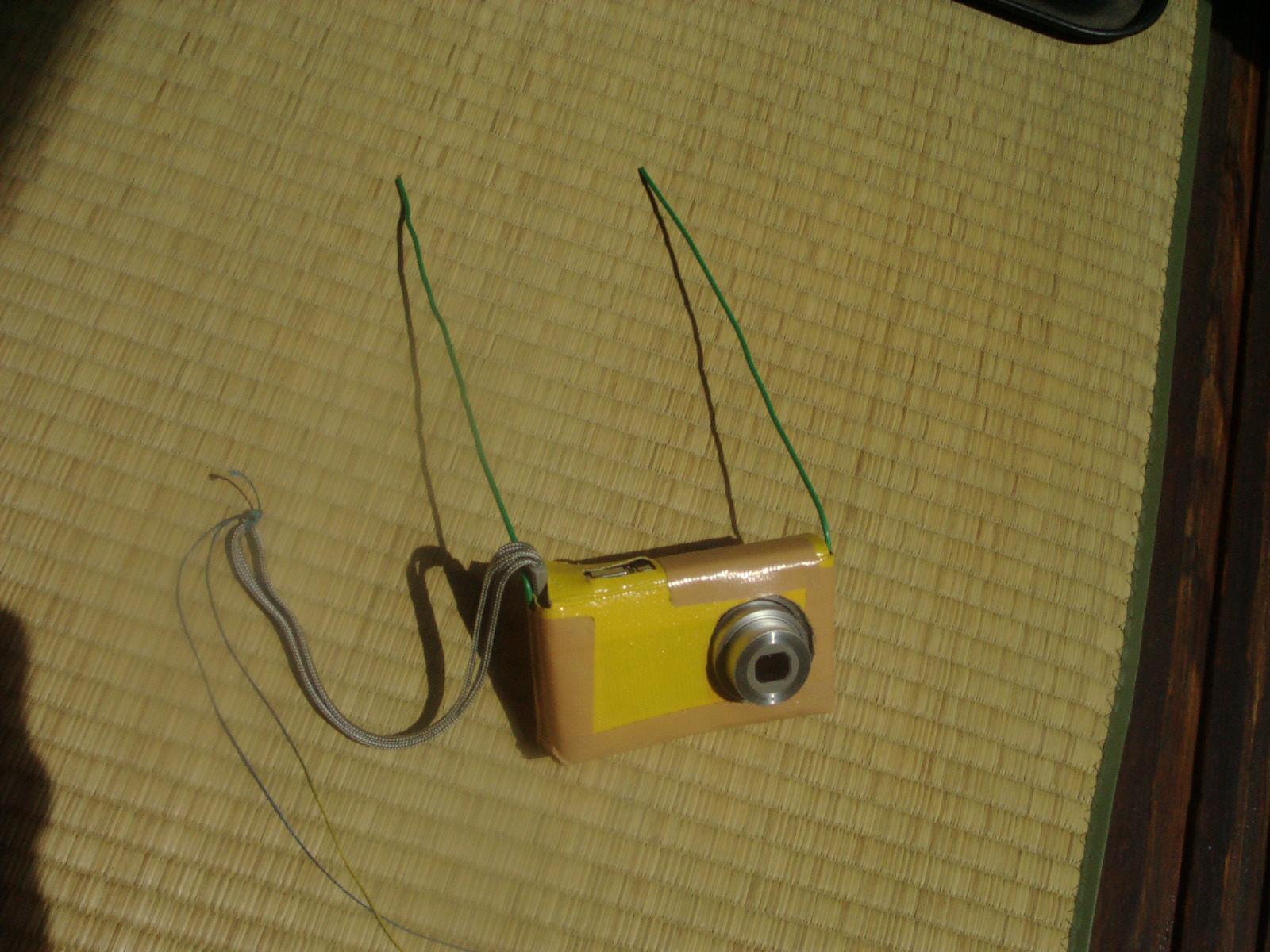 布テープを貼り合せ針金を取り付けただけのこのケースをカイトの骨組みに取り付けるだけのシンプルな方法で空撮を楽しんでいます。 :: 85_1.jpg  : 788 KB